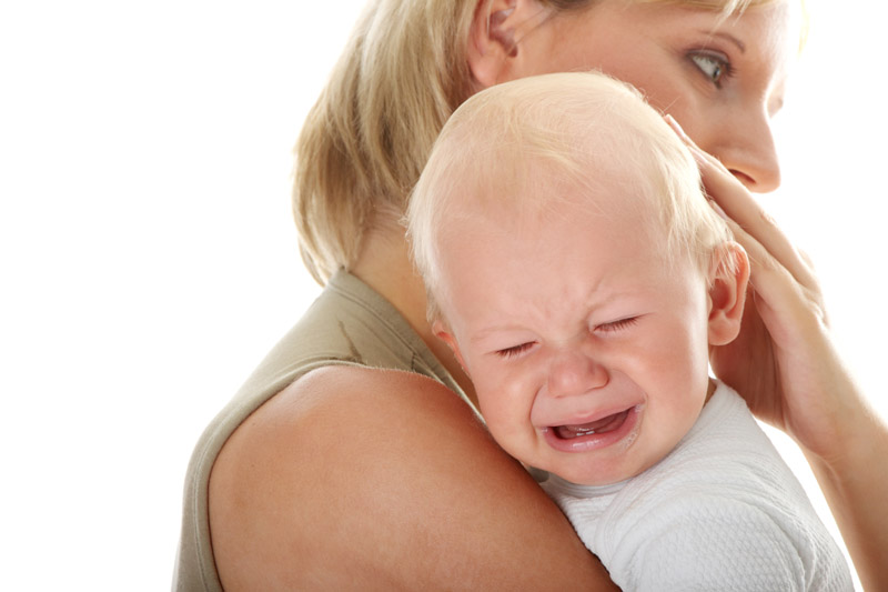 Mother holding her crying baby isolated on white background